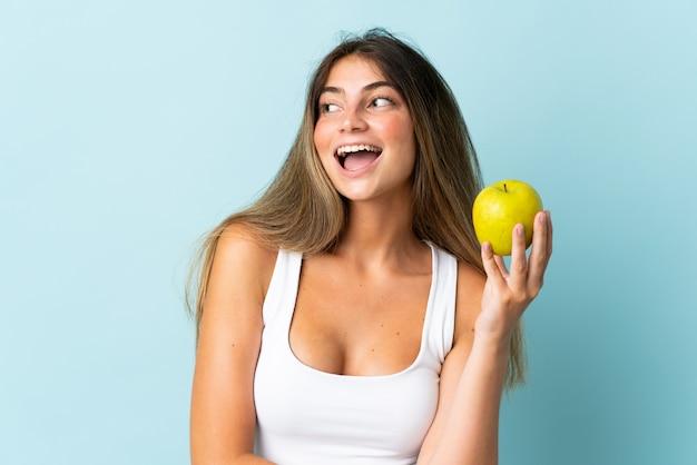 Młoda kobieta kaukaski odizolowana na niebiesko z jabłkiem i szczęśliwa