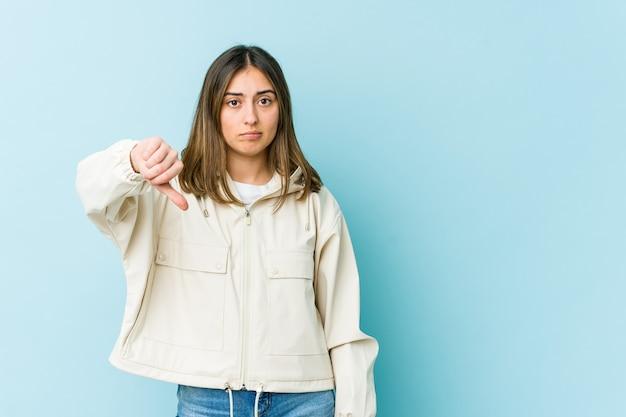 Młoda kobieta kaukaski pokazując gest niechęci, kciuki w dół. pojęcie sporu.
