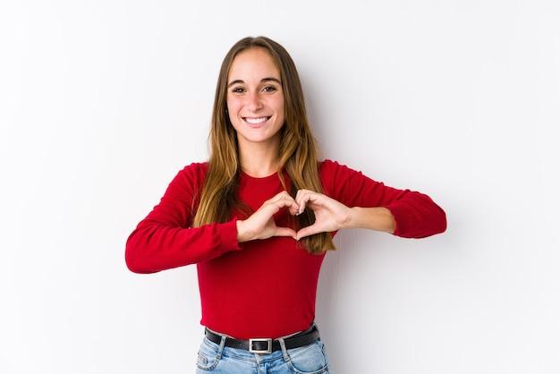 Młoda kobieta kaukaski pozowanie na białym tle, uśmiechając się i pokazując kształt serca rękami.