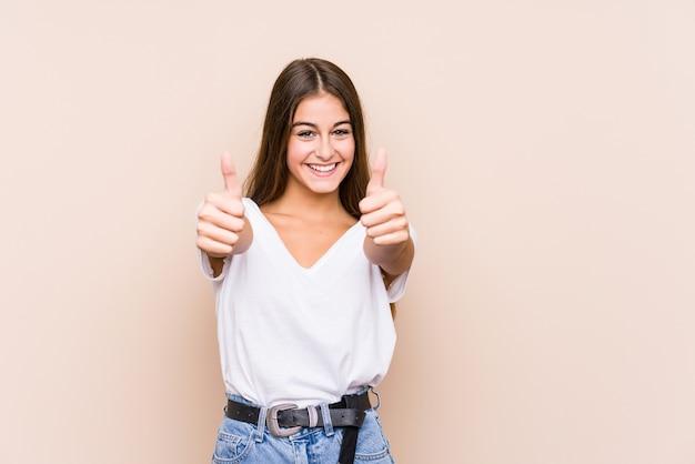 Młoda kobieta kaukaski pozowanie na białym tle z kciuki do góry, wiwaty na temat czegoś, wsparcie i szacunek koncepcji.