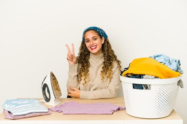 Młoda kobieta kaukaski prasowanie odzieży na białym tle wyświetlono numer dwa palcami.