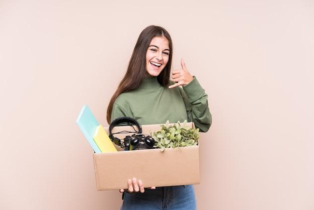 Młoda kobieta kaukaski przenosi się do nowego domu na białym tle przedstawiający gest połączenia telefonu komórkowego palcami.