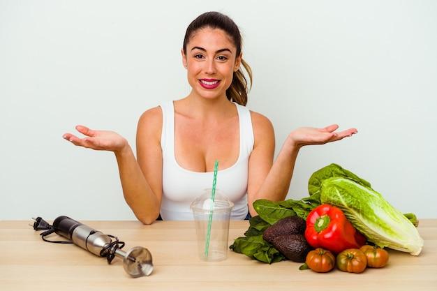 Młoda kobieta kaukaski przygotowuje zdrowy koktajl z warzywami, pokazując mile widziane wyrażenie.