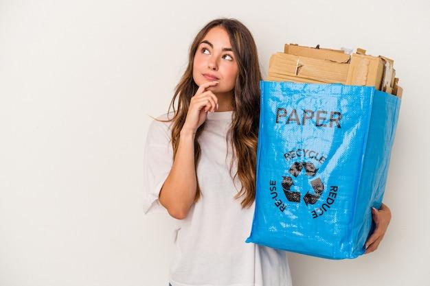 Młoda kobieta kaukaski recyklingu papieru na białym tle patrząc w bok z wyrazem wątpliwości i sceptyczny.
