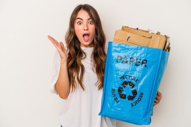 Młoda kobieta kaukaski recyklingu papieru na białym tle zaskoczony i zszokowany.