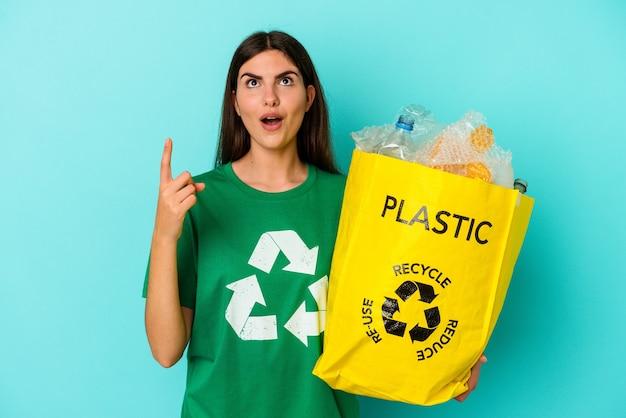 Młoda kobieta kaukaski recyklingu tworzyw sztucznych na białym tle na niebieskim tle, wskazując do góry z otwartymi ustami.