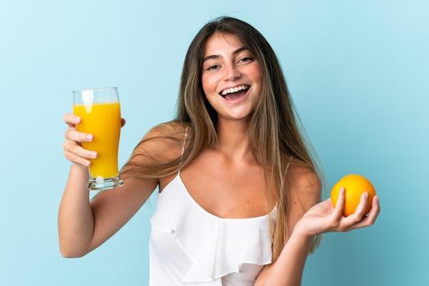 Młoda kobieta kaukaski samodzielnie na niebiesko trzyma sok pomarańczowy i pomarańczowy