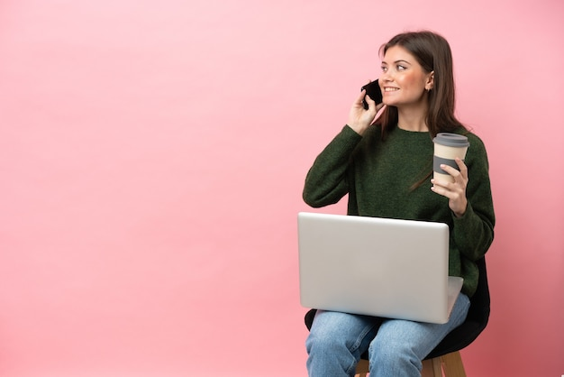 Młoda kobieta kaukaski siedzi na krześle z laptopem na białym tle na różowym tle trzymając kawę na wynos i telefon komórkowy