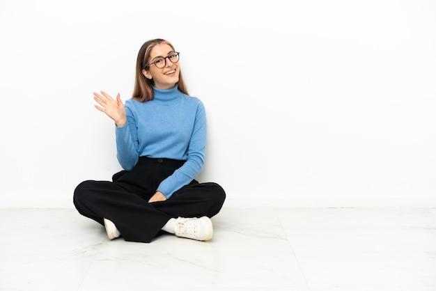 Młoda kobieta kaukaski siedzi na podłodze pozdrawiając ręką z happy wypowiedzi
