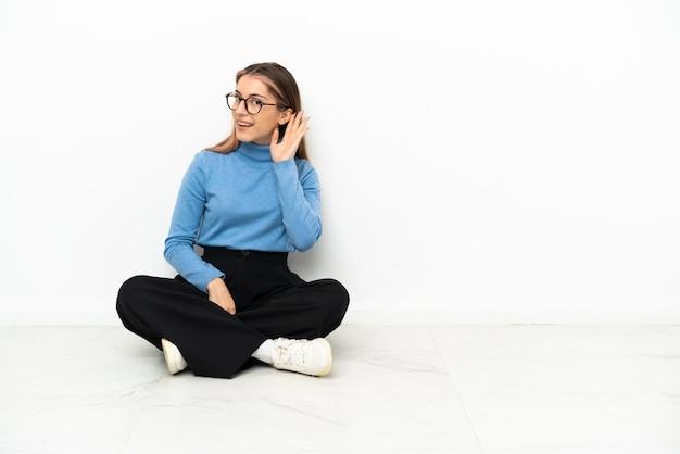 Młoda kobieta kaukaski siedzi na podłodze, słuchając czegoś, kładąc rękę na uchu