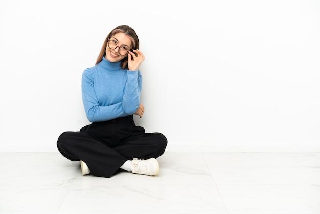 Młoda kobieta kaukaski siedzi na podłodze w okularach i szczęśliwy