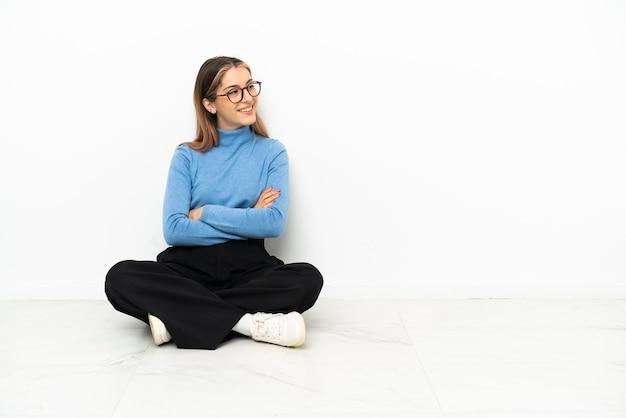 Młoda kobieta kaukaski siedzi na podłodze z rękami skrzyżowanymi i szczęśliwa