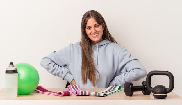Młoda kobieta kaukaski siedzi przy stole ze sprzętem sportowym na białym tle pewnie trzymając ręce na biodrach.