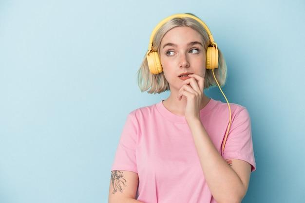 Młoda kobieta kaukaski słuchania muzyki na białym tle na niebieskim tle zrelaksowany, myśląc o czymś, patrząc na miejsce na kopię.