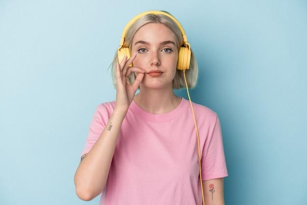 Młoda kobieta kaukaski słuchanie muzyki na białym tle na niebieskim tle z palcami na ustach zachowując tajemnicę.