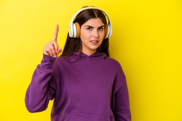Młoda kobieta kaukaski, słuchanie muzyki w słuchawkach na białym tle na różowej ścianie, mając pomysł