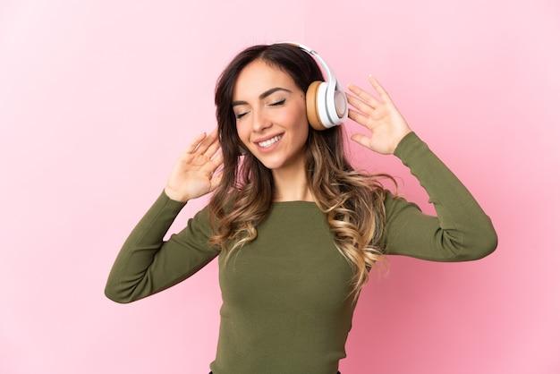 Młoda kobieta kaukaski słuchanie muzyki z telefonu komórkowego i śpiewu na pojedyncze ściany