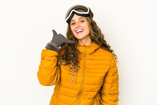 Młoda kobieta kaukaski snowboardzista na białym tle pokazano gest połączenia telefonu komórkowego z palcami.