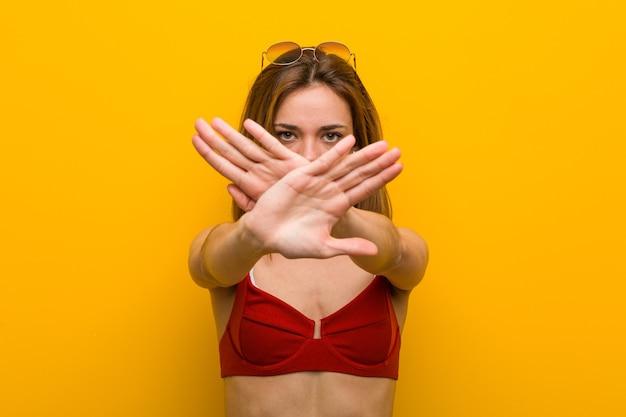 Młoda kobieta kaukaski sobie bikini i okulary przeciwsłoneczne robi gest odmowy