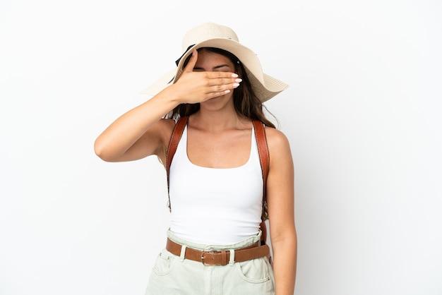 Młoda kobieta kaukaski sobie pamela w wakacje na białym tle na białym tle zakrywając oczy rękami. nie chcę czegoś widzieć