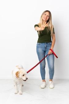 Młoda kobieta kaukaski spacery z psem na białym tle szczęśliwa i licząca cztery palcami