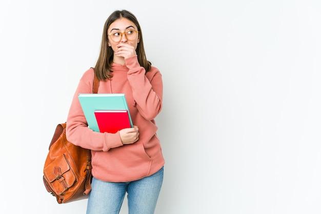 Młoda kobieta kaukaski student na białym tle zamyślony patrząc na przestrzeń kopię obejmującą usta ręką.