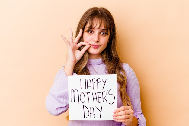Młoda kobieta kaukaski trzyma afisz szczęśliwy dzień matki na białym tle z palcami na ustach, zachowując tajemnicę.