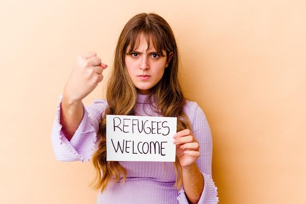 Młoda kobieta kaukaski trzymając afisz powitalny uchodźców na białym tle pokazując pięść, agresywny wyraz twarzy.