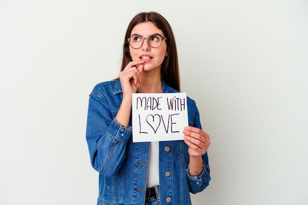 Młoda kobieta kaukaski trzymając afisz wykonane z miłością na białym tle patrząc w bok z wyrazem wątpliwości i sceptycyzmu.