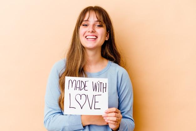 Młoda kobieta kaukaski trzymając afisz wykonane z miłością na białym tle śmiechu i zabawy.