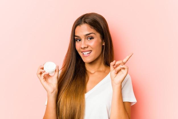 Młoda kobieta kaukaski trzymając balsam uśmiechnięty radośnie, wskazując palcem wskazującym z dala.