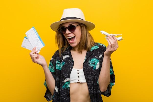 Młoda kobieta kaukaski trzymając bilety lotnicze bardzo szczęśliwy.
