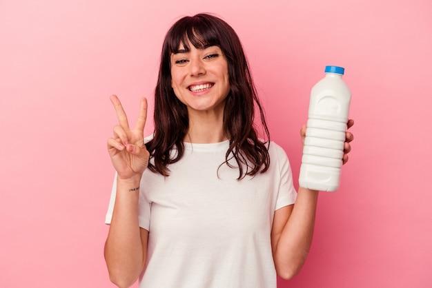 Młoda kobieta kaukaski trzymając butelkę mleka na białym tle na różowej ścianie pokazuje numer dwa palcami