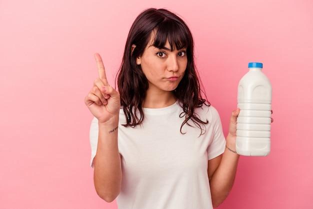 Młoda kobieta kaukaski trzymając butelkę mleka na białym tle na różowym tle pokazuje numer jeden z palcem.
