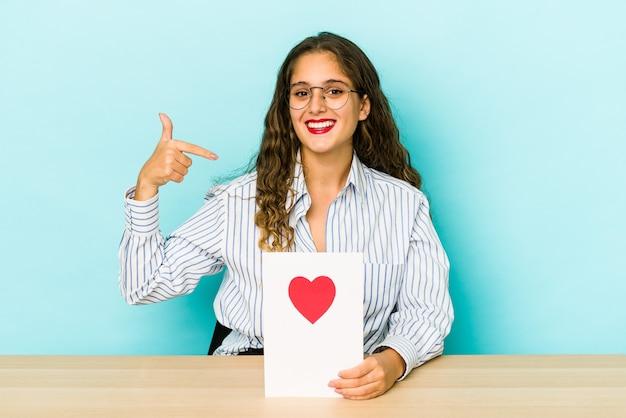 Młoda kobieta kaukaski trzymając kartę walentynki na białym tle osoba, wskazując ręką na przestrzeni kopii koszuli, dumny i pewny siebie