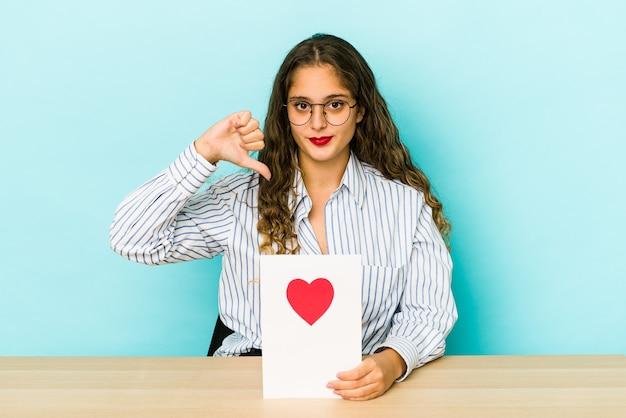 Młoda kobieta kaukaski trzymając kartę walentynki na białym tle pokazując niechęć gest, kciuk w dół. pojęcie sporu.