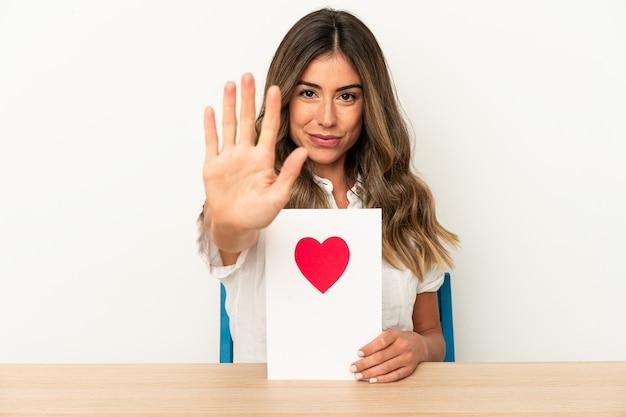 Młoda kobieta kaukaski trzymając kartę walentynki na białym tle stojąc z wyciągniętą ręką pokazując znak stopu, uniemożliwiając ci.