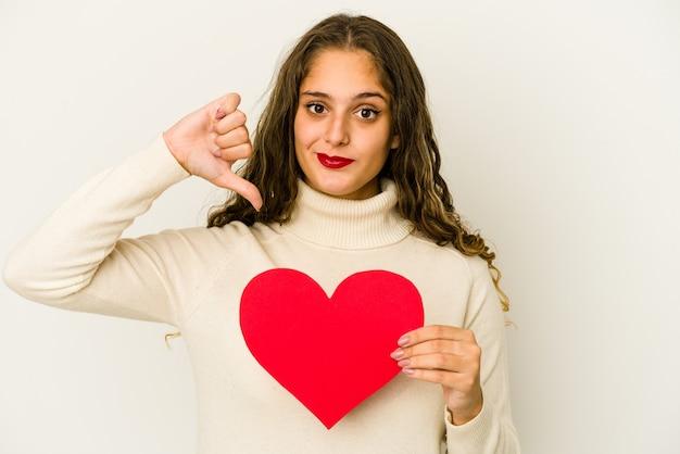 Młoda kobieta kaukaski trzymając kształt serca walentynki na białym tle pokazując niechęć gest, kciuk w dół. pojęcie sporu.