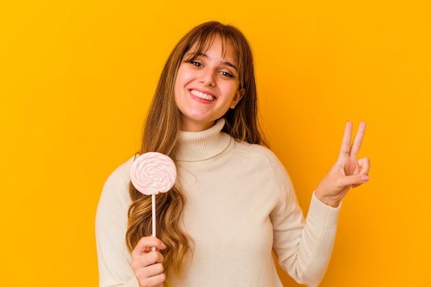Młoda kobieta kaukaski trzymając lizaka na białym tle na żółtej ścianie pokazuje numer dwa palcami.