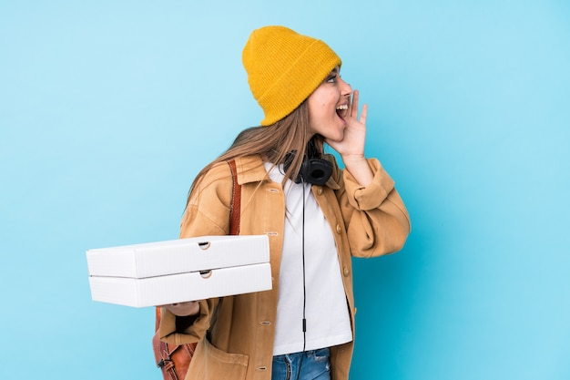Młoda kobieta kaukaski trzymając pizze na białym tle, krzycząc i trzymając dłoń w pobliżu otwartych ust.