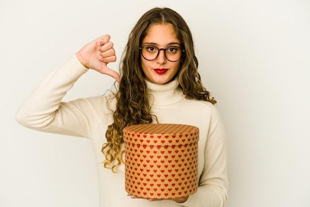 Młoda kobieta kaukaski trzymając pudełko walentynki serca na białym tle pokazuje niechęć gest, kciuk w dół. pojęcie sporu.