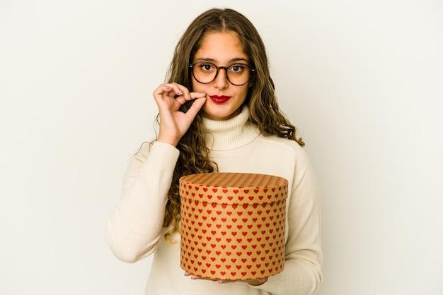 Młoda kobieta kaukaski trzymając pudełko walentynki serca na białym tle z palcami na ustach, zachowując tajemnicę.