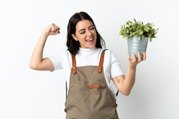 Młoda kobieta kaukaski trzymając roślinę na białym tle