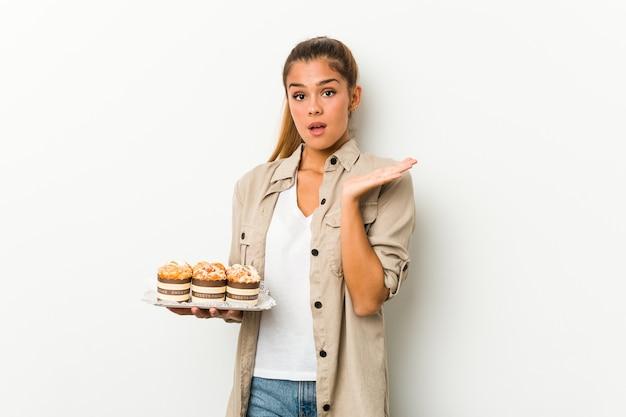 Młoda kobieta kaukaski trzymając słodkie ciasta zaskoczony i zszokowany.