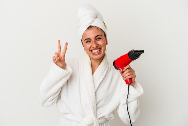 Młoda kobieta kaukaski trzymając suszarkę do włosów na białym tle pokazuje numer dwa palcami.