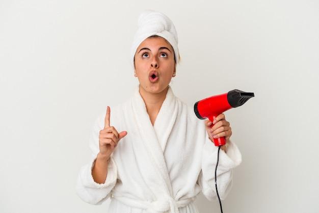 Młoda kobieta kaukaski trzymając suszarkę do włosów na białym tle, wskazując do góry z otwartymi ustami.