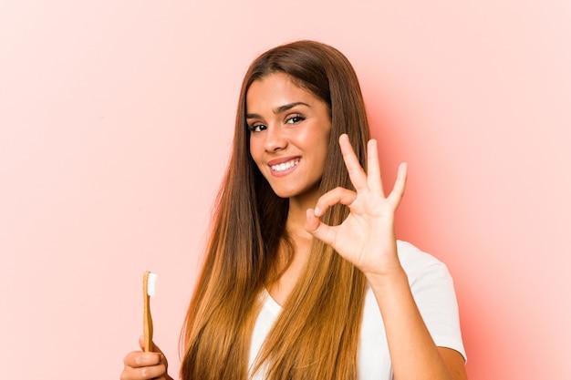 Młoda kobieta kaukaski trzymając szczoteczkę do zębów, wesoły i pewny siebie, pokazując ok gest.