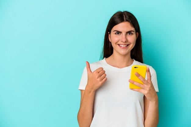 Młoda kobieta kaukaski trzymając telefon komórkowy na białym tle na niebieskiej ścianie uśmiechając się i podnosząc kciuk do góry