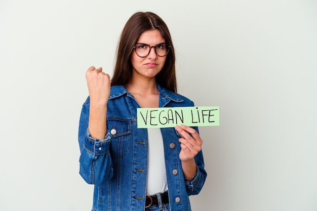 Młoda kobieta kaukaski trzymając wegańską tabliczkę życia na białym tle na białej ścianie, wskazując w bok