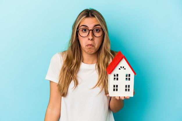 Młoda kobieta kaukaski trzymająca model domu wzrusza ramionami i zdezorientowana otwartymi oczami.
